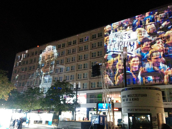 People celebrating the 30th anniversary of the fall of the Berlin Wall illuminated on a building in the city's Alexanderplatz public square, located near the site of QWS2019.