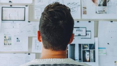 back of man's head in front of whiteboard with design notes on it